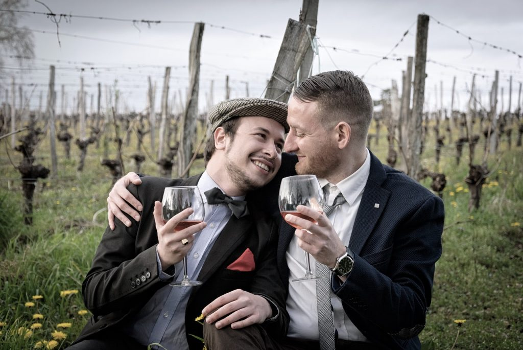 Couple of men, happy, smiling and drinking wine