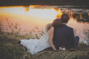 A recent wedding couple sit to see sunset